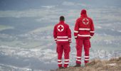 Salzburg, Austria - December 30, 2013: Two rescuers look down at the city of Salzburg from the Gaisberg. Is the emblem of the Red Cross on her back. From the summit of the mountain is a paragliding take-off and landing area. Again and again happen at this place accidents. So also on this day.